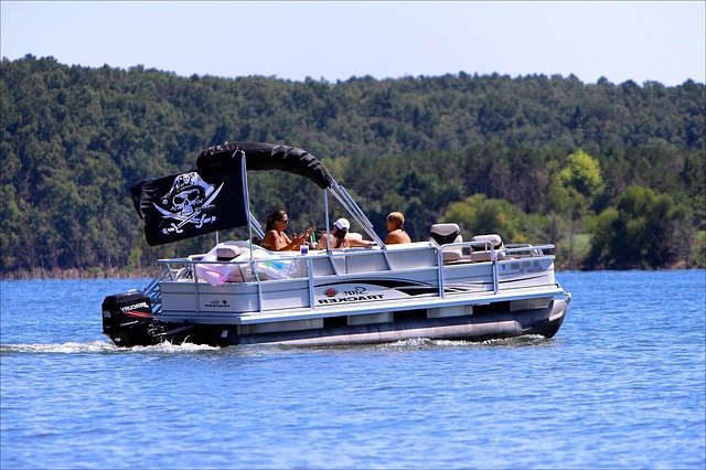 people relaxing on pontoon boat with pirate flag