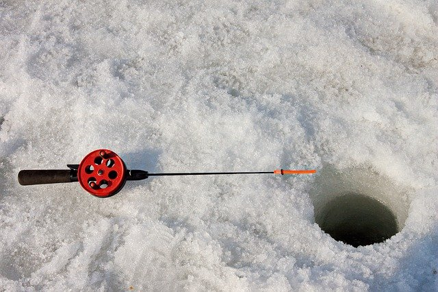 ice fishing hole and rod in snow
