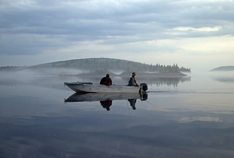 boat fishing and trolling on calm lake