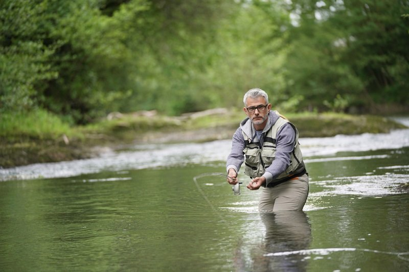 person fly fishing for trout