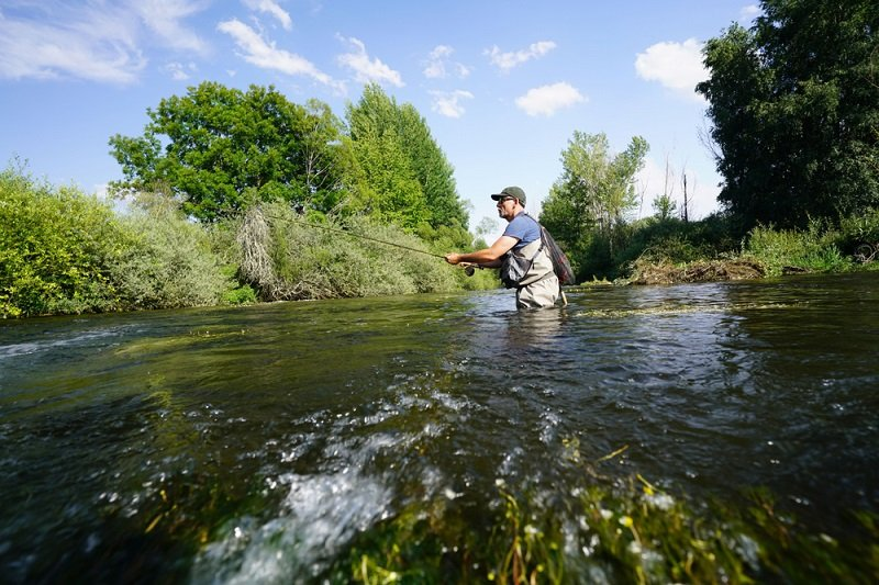 man fly fishing in moving stream