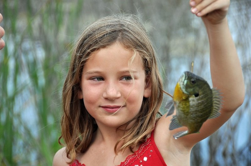girl holding bluegill fish